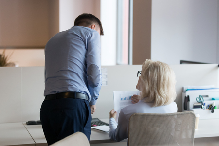 Photo pour Businessman and mature businesswoman working on financial report together, colleagues discussing project result, analyzing statistics, mentor with trainee, boss check subordinate work rear view - image libre de droit