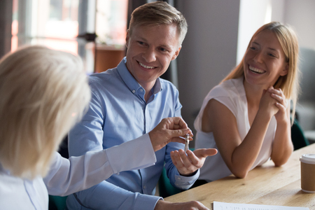 Photo pour Smiling man receiving keys from new house, making deal with realtor in office, tenants signing lease agreement with mature manager, taking loan or mortgage, client purchasing property, real estate - image libre de droit