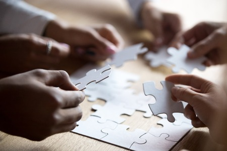 Photo pour Close up members of multiracial team assembling white puzzle, African American and Caucasian people searching solution together, team building activity, staff training, support and unity - image libre de droit