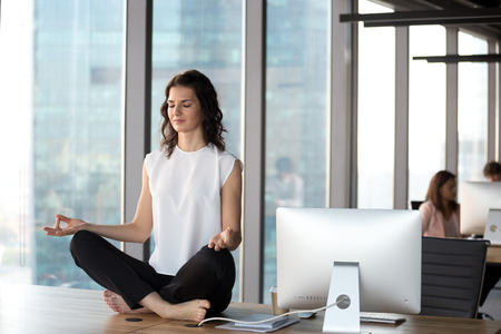 Peaceful millennial businesswoman sit at office table practicing yoga in lotus position, calm female employee meditating in coworking space, breathing deep clearing mind. Stress free conceptの素材 [FY310124263657]