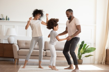 Happy funny active african family with cute little kid daughter dancing at home, carefree cheerful black parents mom dad and small child girl having fun jumping laughing enjoy leisure in the morning