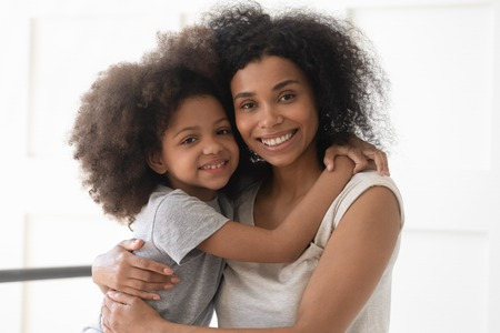 Photo pour Beautiful african american family young single mother and cute little child daughter embrace bonding looking at camera sit on bed together, happy black mom with small kid girl hug in bedroom portrait - image libre de droit