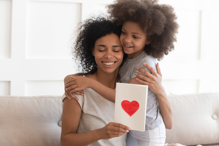 Photo pour Happy young african american single mom embracing little cute child daughter thanking for gift, smiling black mum hugging small kid holding greeting card with red heart bonding on mothers day concept - image libre de droit