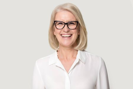 Foto de Head shot portrait laughing old businesswoman in glasses white blouse looks at camera feels happy pose isolated on grey studio background, experienced professional business coach teacher concept image - Imagen libre de derechos