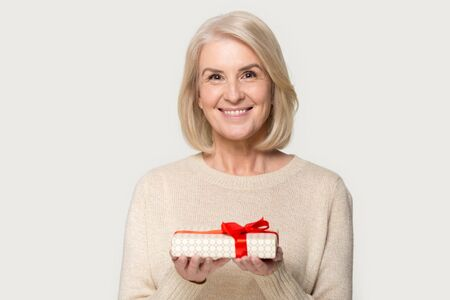 Foto de Attractive aged blond woman looks at camera holding presents gift box red bow package feels happy studio head shot isolated on grey background. Life events celebration congratulation love care concept - Imagen libre de derechos