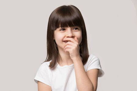 Photo pour Head shot little shy brown-eyed brown-haired girl cover mouth when laughing feel embarrassment, preschool funny kid giggling stands isolated on grey studio background, have fun chuckle at joke concept - image libre de droit
