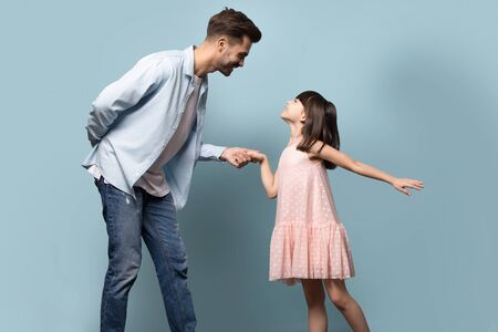 Photo for Elder brother younger sister dancing waltz enjoy time together, loving young father gentleman and little daughter princess in pink dress standing holding hands family pose isolated on blue background - Royalty Free Image