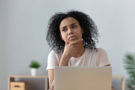 Photo pour Thoughtful doubtful african female student worker looking away thinking solving problem feel lack of new creative ideas at work, pensive puzzled or bored young black woman sit at desk with laptop - image libre de droit