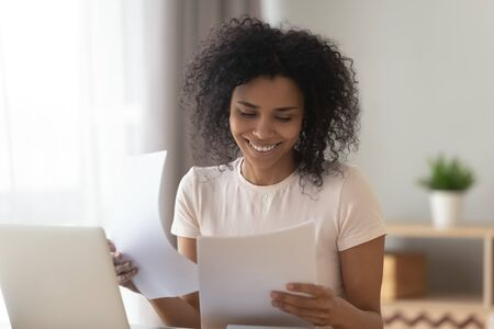 Photo pour Happy young african american woman sit at table reading good news in paper letter checking domestic bills, smiling black holding documents doing paperwork work or study sit at home office desk - image libre de droit