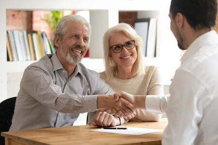 Photo pour Happy senior old family couple clients make financial insurance estate business deal handshake agent lawyer, satisfied mature customers shake hand meeting bank manager agree on investment contract - image libre de droit