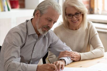 Foto de Happy older family couple husband and wife sign legal paper insurance contract write will testament, senior clients customers put signature on business document make financial deal take bank loan - Imagen libre de derechos