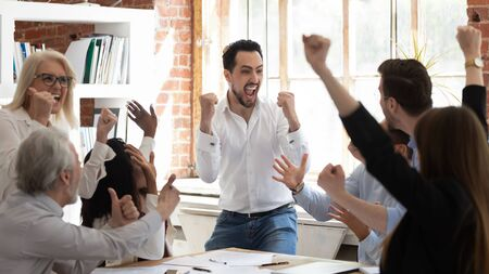 Foto de Euphoric excited business team celebrate corporate victory together in office, happy overjoyed professionals group rejoice company victory, teamwork success win triumph concept at conference table - Imagen libre de derechos