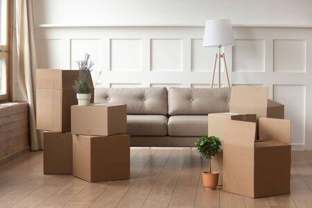 Foto de Moving day concept, cardboard carton boxes stack with household belongings in modern house living room, packed containers on floor in new home, relocation, renovation, removals and delivery service - Imagen libre de derechos