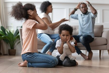 Photo pour Upset african kids closing ears hurt by parents fighting arguing at home, sad stressed little innocent children suffer from family problems conflicts, unhappy mom dad shouting quarreling divorcing - image libre de droit