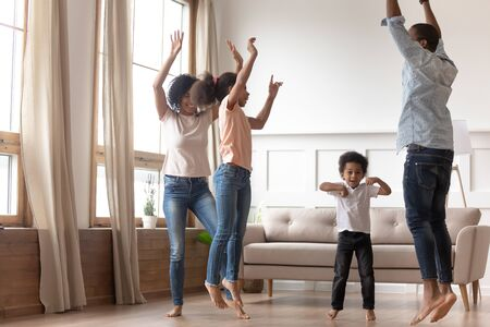Foto de Joyful happy african family having fun jumping in living room together, active black parents and little cute kids dancing at home, mixed race mom dad with small kids laughing enjoy leisure activity - Imagen libre de derechos