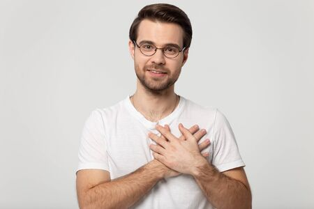 Head shot portrait attractive guy in white t-shirt look at camera feel grateful, man holds hands on chest heart symbol of love, moment of sincere gratitude and thankfulness isolated on gray background
