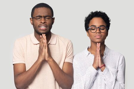 Superstitious ethnic millennial couple wearing glasses isolated on grey studio background hold hands in prayer, hopeful black biracial man and woman believer pray make wish hope for best