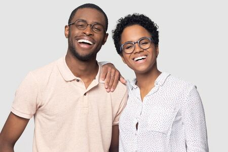 Photo pour Headshot portrait of overjoyed african American couple in glasses isolated on grey studio background laugh look at camera, happy ethnic black man and woman smiling posing for picture together - image libre de droit