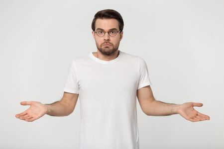 Confused young man wearing white t-shirt glasses being in perplexity, guy shrugged his shoulders look at camera feel puzzled isolated on gray studio background ambiguous situation, I dont know concept