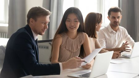 Foto de Caucasian male manager mentor teach consult asian female client intern about contract online project looking at laptop sit at desk in office, happy korean trainee customer learn new skills get advice - Imagen libre de derechos