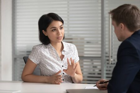Foto de Female asian bank manager insurer job applicant talk to male hr consult customer at interview meeting, japanese broker explain deal benefits to client make offer, recruit and business advice concept - Imagen libre de derechos