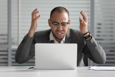 Photo pour Angry stressed african business man using laptop mad about broken computer online problem annoyed with slow stuck laptop error, crazy about system virus or data loss, outraged with website mistake - image libre de droit