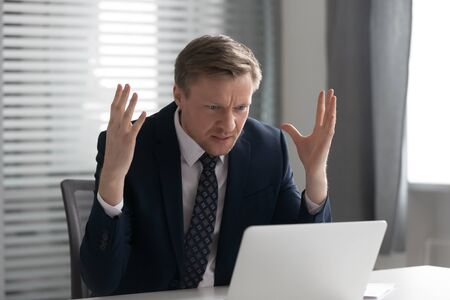 Photo pour Annoyed mad businessman wearing suit frustrated with online problem, angry stressed male professional using laptop outraged by broken pc, crazy about stuck slow computer virus app error at workplace - image libre de droit