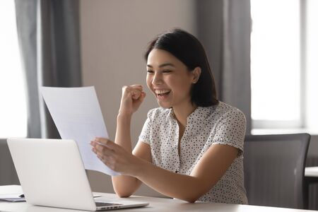 Photo for Happy asian business woman celebrate success great achievement work result look at financial report, excited japanese student winner read good news in paper letter overjoyed by admission scholarship - Royalty Free Image