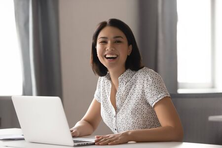 Foto de Happy asian business woman laughing sitting at work desk with laptop, cheerful smiling female chinese employee having fun feeling joy and positive emotion express sincere laughter at office workplace - Imagen libre de derechos