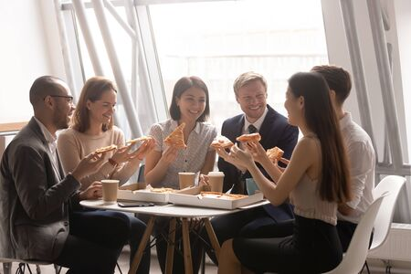 Happy friendly multi ethnic business team people having fun eating pizza together in office, smiling diverse workers staff group talk laugh share lunch food dinner meal enjoying party at work break
