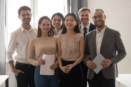 Foto de Multicultural professional work team happy company employees group looking at camera stand in office, smiling diverse corporate staff workers business people posing together, human resource portrait - Imagen libre de derechos