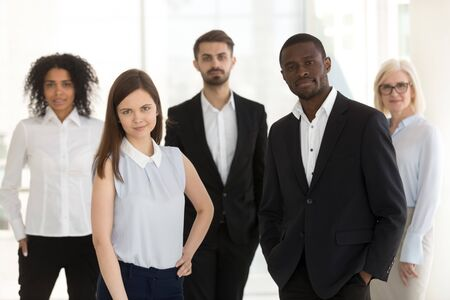 Portrait of diverse confident work team looking at camera, successful multiethnic managers posing for photo in office together, employees motivated for success or business achievement