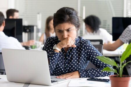 Photo for Focused worried Indian businesswoman looking at laptop screen, doubting, thinking of difficult question or task, female employee upset by receiving bad news, tired office worker have too much work - Royalty Free Image