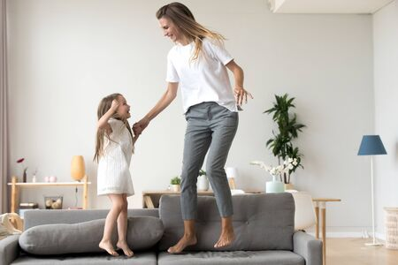 Photo pour Little adorable daughter happy young mommy elder sister or babysitter hold hands jumping together on sofa in living room at home. Cheerful mom cute excited child spend free time on weekend having fun - image libre de droit
