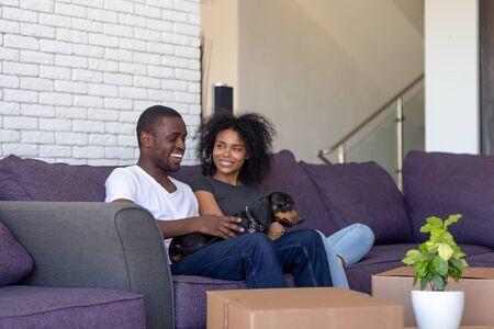 Photo pour African couple wife husband resting on sofa with dachshund dog in living room on moving day delivered boxes with unpacked belongings. Buyers of first house, loan mortgage relocation, new life concept - image libre de droit