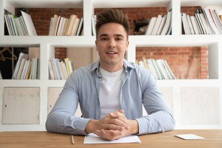 Foto de Serious millennial male coach or speaker sit at desk record online training or study course, focused young tutor talk with viewers shoot live tutorial, make video broadcast with internet subscribers - Imagen libre de derechos