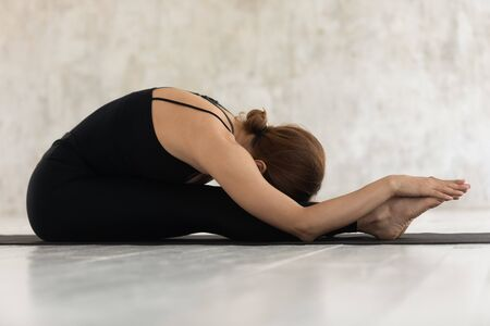 Photo pour Young sporty woman wearing black shirt and leggings clothing performing Paschimottanasana exercise Seated Forward Bend pose side view, do asana on mat, practising yoga, mental physical health concept - image libre de droit