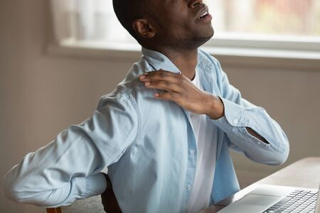 Cropped close up image african guy sit at table in front of pc touching shoulder suffers painful sensations in lower back, sedentary work, devices overuse long time usage sitting wrong posture concept