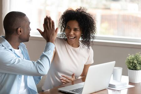 Photo pour Happy african husband biracial wife couple sit at table near computer make fists yes gesture celebrating victory feels overjoyed unbelievable luck online lottery win betting, mortgage approval concept - image libre de droit
