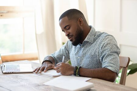 Photo for Focused african american man student freelancer making notes studying working with laptop, young black man professional writing essay in notebook preparing for test exam sit at home office desk - Royalty Free Image