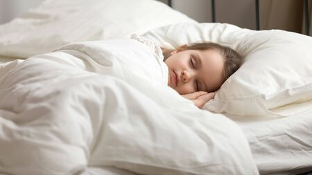 Photo pour Calm adorable little daughter take day nap. Tranquil preschool child girl covered with white fresh duvet lying in bed comfortable mattress on bedroom. Healthy enough sleeping, zzz, good night, concept - image libre de droit