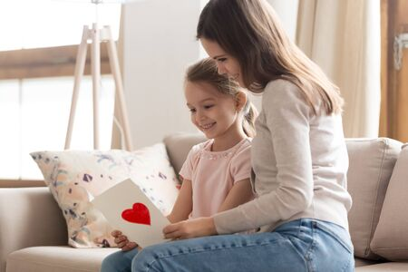 Photo for Mother and adorable daughter sitting on couch in living room read wishes text on handmade postcard, beautiful sisters looking at paper card, attentive kid made gift on international womens day concept - Royalty Free Image