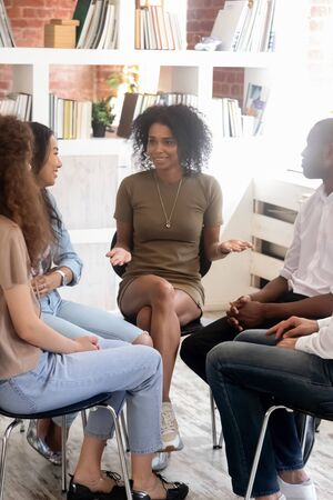 Foto de Vertical image diverse people sitting on chairs in circle listen psychologist telling personal stories at rehab group. Students gather together gain knowledge informal seminar study education concept - Imagen libre de derechos