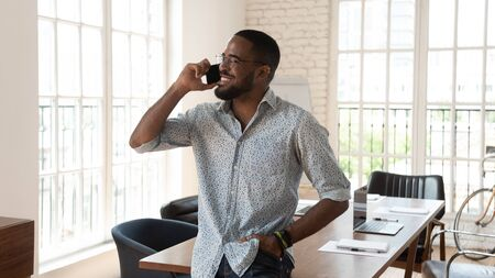 Photo pour Happy african american businessman standing in modern work space talking on phone, smiling young black entrepreneur startup owner speak on cellphone enjoy mobile conversation in creative office - image libre de droit
