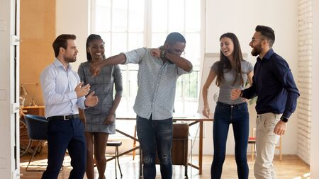 Foto de Happy funny motivated diverse business team people celebrating success win or enjoying corporate party in victory dance, positive friendly multiracial coworkers dancing in office having fun together - Imagen libre de derechos