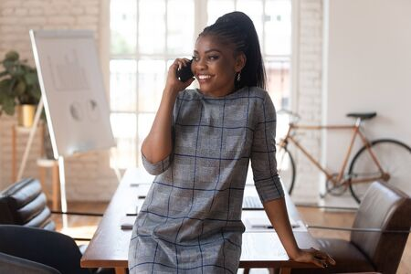 Photo pour Smiling black businesswoman manager talking on phone making business call at work, happy female african american executive having mobile conversation consult client by mobile in modern office space - image libre de droit