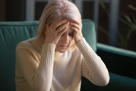 Upset stressed tired old mature woman feel pain coping with headache concept, fatigued dizzy frustrated senior middle aged lady touching head suffer from migraine vertigo high blood pressure at home