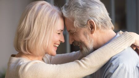 Photo pour Loving old senior family couple bonding embracing touching foreheads, romantic middle aged mature man and woman hugging getting closer enjoying moment of affection cuddling, close up side view - image libre de droit