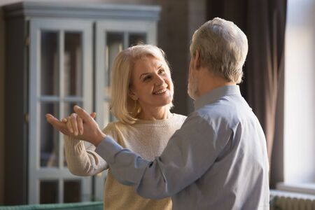 Happy romantic old senior couple dancing waltz at home, healthy mature grandparents enjoy tender moment of love in slow dance, smiling elder middle aged family spouses relaxing bonding together