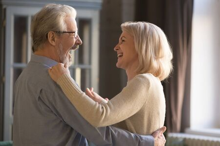 Foto de Happy loving elder senior husband laughing holding middle aged wife dancing at home, cheerful retired beautiful married couple and wife having fun relaxing together enjoy retirement lifestyle - Imagen libre de derechos